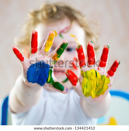 Portrait of cute cheerful girl with painted hands
