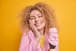 Portrait of cute cheerful woman with curly hair keeps hand on cheek smiles gently holds tasty ice cream feels temptation to eat sweet cold dessert expresses happiness isolated over yellow background