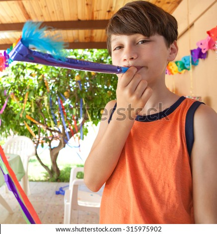 Portrait of cute child boy playing with a colorful party blower in a sunny summer birthday party in a home garden, outdoors. Kid having fun and smiling on a summer holiday, home exterior.
