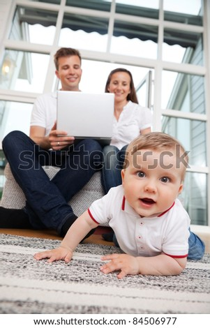 Portrait of cute child with parents using laptop in the background
