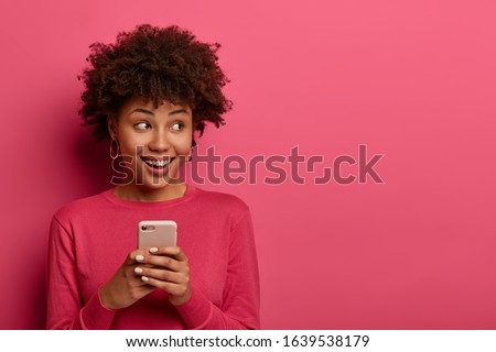 Portrait of cute curly haired girl scrolls social networks or does shopping online, looks aside positively, uses modern smartphone, wears pink sweater, poses indoor in studio, reads message.