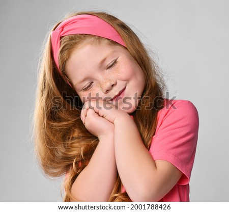 Portrait of cute daydreaming redhead kid girl in pink t-shirt and headband holding hands together at cheek, eyes closed, sleeping Foto stock ©