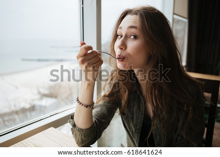 Portrait of cute eating woman with spoon sitting near window in cafe
