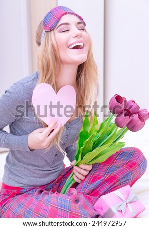Portrait of cute excited woman with romantic letter and laughing with closed eyes, awake and surprised of gentle romantic presents on Valentine\'s day