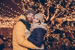 Portrait of cute family hugging each other and smiling while having a stroll at x mas evening in the town, in warm outfits, headwear, many sparkling decorations on the background