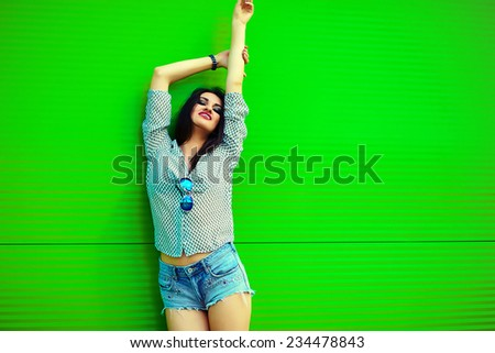 Stock Photo portrait of cute funny sexy young stylish smiling woman girl model in bright modern cloth in jeans shorts with pink lips perfect sunbathed body outdoors in the city near green wall
