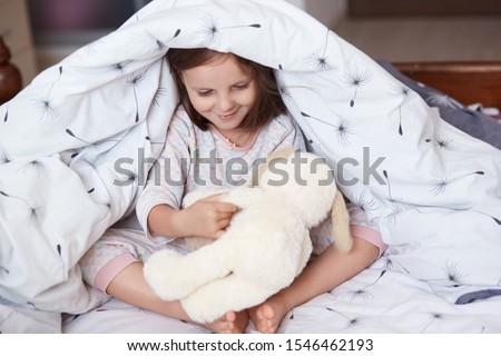 Portrait of cute girl and dog toy under blanket, little female kid and dog toy playing together games under white blanket, chirming child spending morning time in cosy room. Childhood concept. Stock photo ©