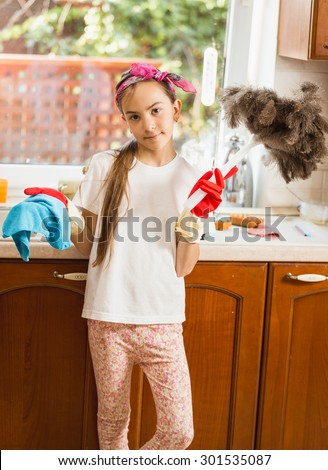 Portrait of cute girl cleaning mess on kitchen with cloth and brush