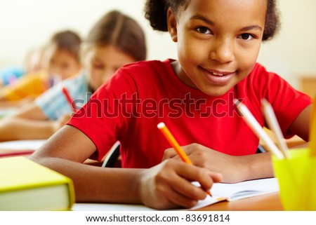 Portrait of cute girl drawing with crayons at lesson
