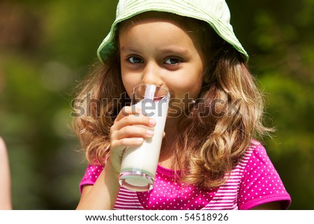 Portrait of cute girl drinking kefir outdoors