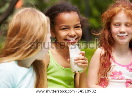 Portrait of cute girl drinking kefir outdoors with her friends near by