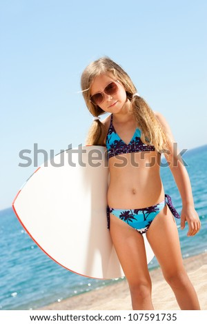 Portrait Of Cute Girl In Bikini Holding White Surfboard On