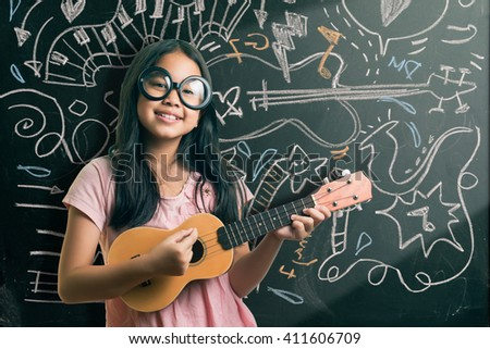 Portrait of cute girl in eyeglasses playing guitar by the blackboard with chalk drawings of musical instruments. - Shutterstock ID 411606709