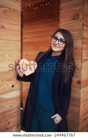 Portrait of cute girl in glasses holding little red gift box, enjoying present with romantic relationship, Valentine day, love and happiness concept