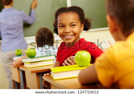 Portrait of cute girl looking at classmate at lesson