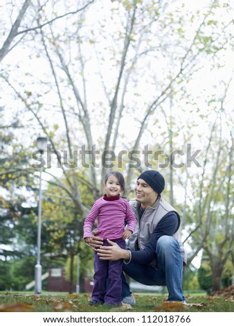 Portrait of cute girl standing with father at park