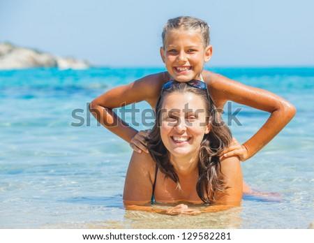 Portrait of cute girl swimming with her mother in the transparent sea