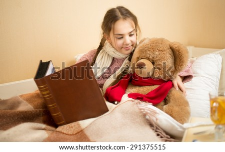 Portrait of cute girl telling story to teddy bear at bed