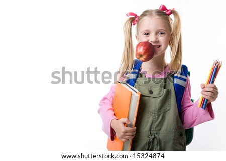 Portrait of cute girl with apple in mouth, book and pencils in hands looking at camera
