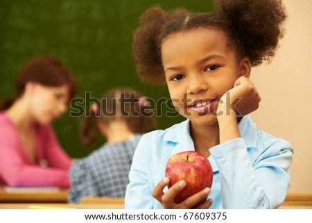 Portrait of cute girl with apple looking at camera during lesson