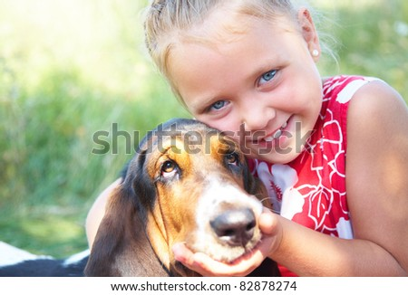 Portrait of cute girl with dog on summer meadow - stock photo
