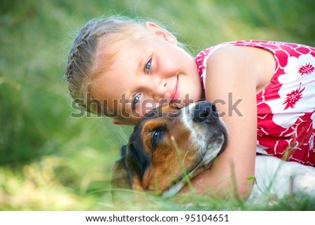 Portrait of cute girl with dog on summer meadow