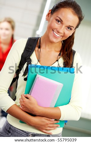 Portrait of cute girl with textbook in hands looking at camera in college