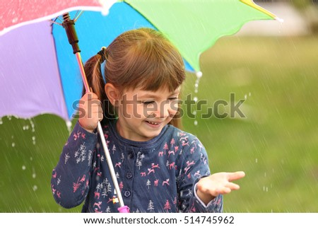 Portrait of cute girl with umbrella in rain #514745962