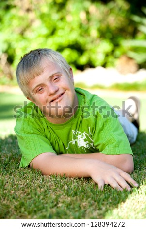 Portrait of cute handicapped boy laying on green grass.