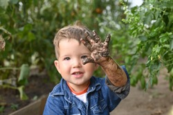 Portrait of cute happy boy showing his muddy hand.
