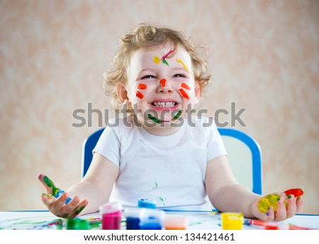 Portrait of  cute happy child with painted hands