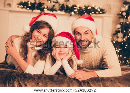 Portrait of cute happy family in santa hats on christmas  on bed