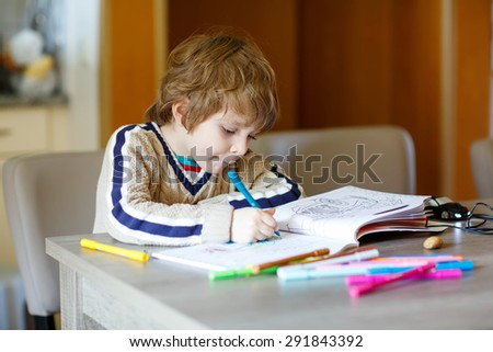 Portrait of cute happy preschool kid boy at home making homework. Little child painting with colorful pencils, indoors.