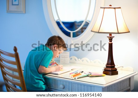 Portrait of cute happy schoolkid at home drawing or writing