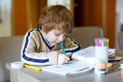 Portrait of cute happy schoolkid at home making homework. Little child painting with colorful pencils, indoors.