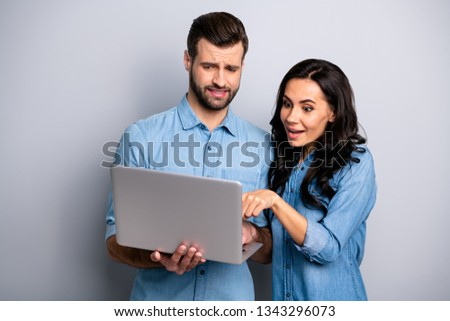 Portrait of cute impressed unsure millennial fellows searching products deciding buy finding news about discount sales prices pointing finger dressed in denim outfit isolated on silver background #1343296073