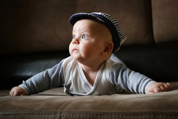 Portrait of cute infant boy lying on sofa and looking aside. Cute 4 month old baby. Infancy, babyhood concept.