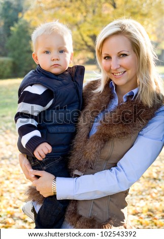 Portrait of cute kid and pretty mom having fun outdoors at fall.
