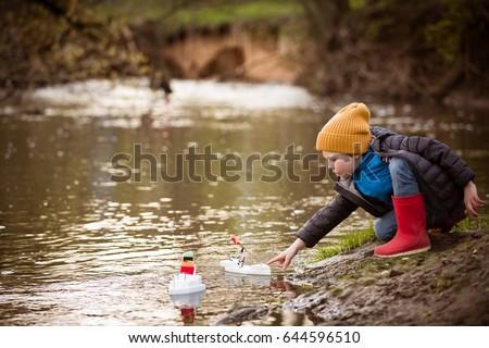 Free photos Creative boy playing paper boats at a lake. | Avopix.com
