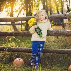Portrait of Cute kid on the farm with flowers in hand. Autumn, early winter