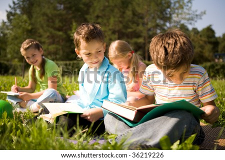 Portrait of cute kids reading books in natural environment together
