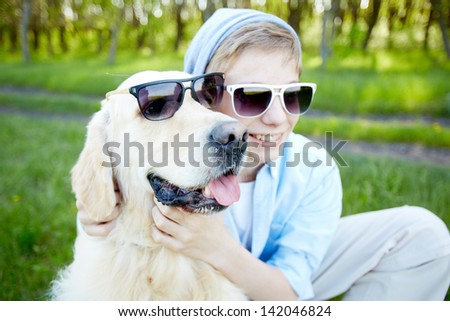 Portrait of cute lad and his fluffy friend in sunglasses outdoors