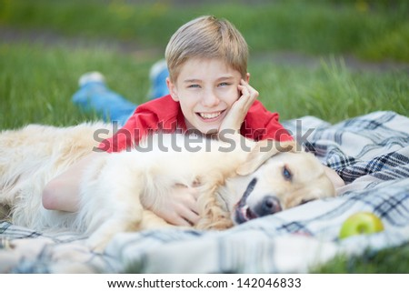 Portrait of cute lad and his fluffy pet lying on plaid