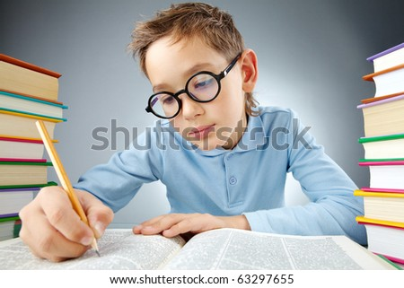 Portrait of cute lad in eyeglasses reading book