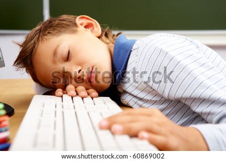 Portrait of cute lad sleeping with his head on computer keyboard in classroom - stock photo