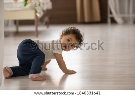 Photo of  Portrait of cute little african American baby toddler crawl make first steps on home wooden floor. Small biracial newborn infant child learn walking play indoors. Childcare, upbringing concept.