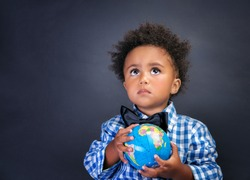 Portrait of cute little African boy holding in hands small globe on blackboard background, back to school concept