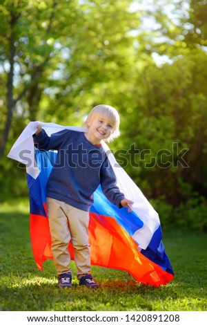 Portrait of cute little boy in public summer park with russian flag on background. Fans child supporting and cheering their national team. Day of independence. Pride and patriotism. #1420891208