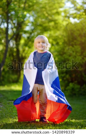 Portrait of cute little boy in public summer park with russian flag on background. Fans child supporting and cheering their national team. Day of independence. Pride and patriotism. #1420898339