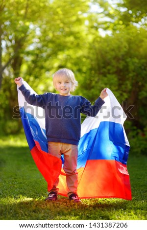 Portrait of cute little boy in public summer park with russian flag on background. Fans child supporting and cheering their national team. Day of independence. Pride and patriotism. #1431387206